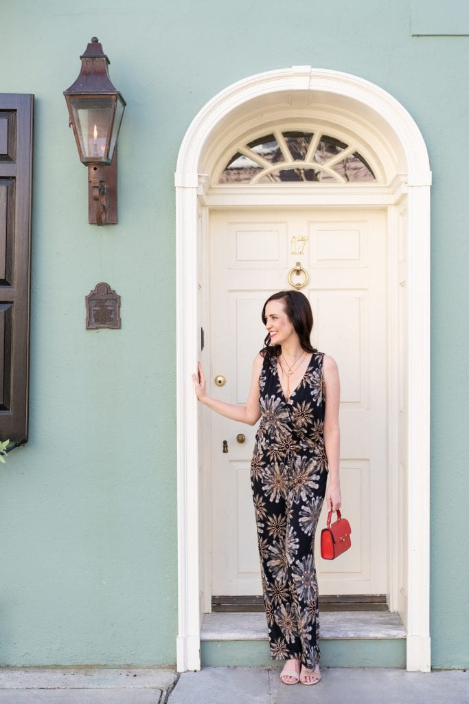 Life With Ashley T standing in a historic Charleston doorway in a jumpsuit