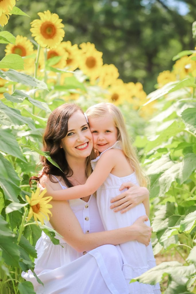 Mother and Daughter hugging in Sunflower Field