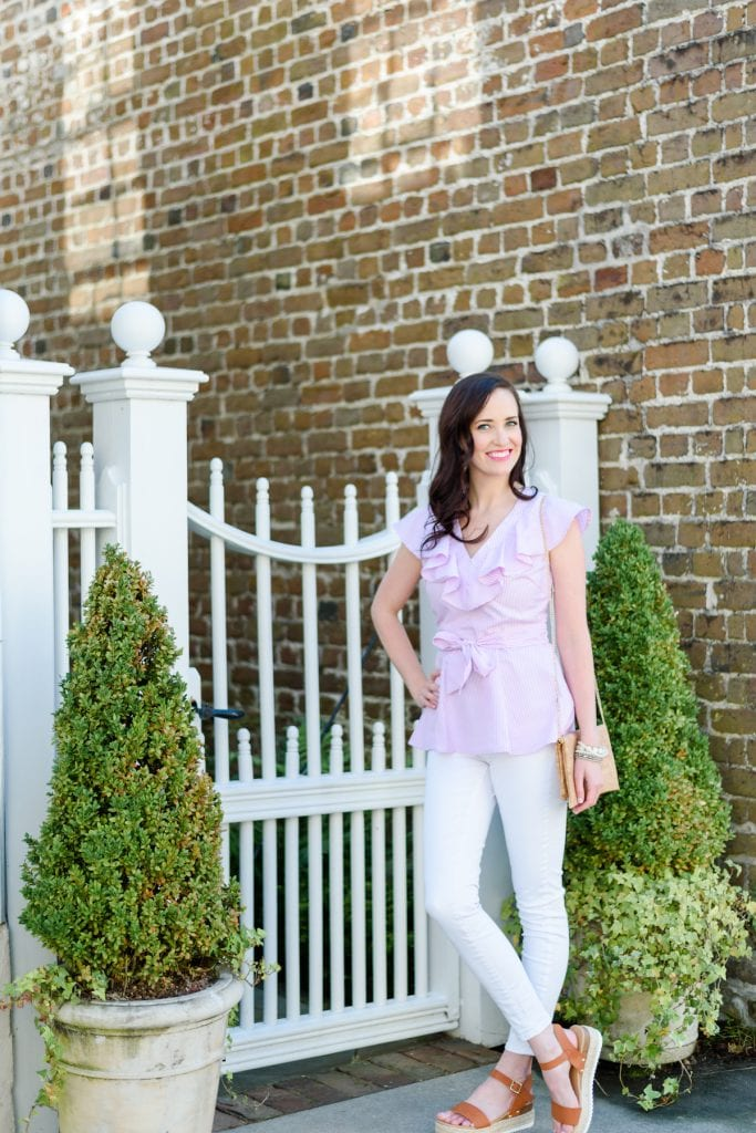 Life With Ashley T in front of a historic Charleston home wearing a spring ruffle top from Map & Co Design