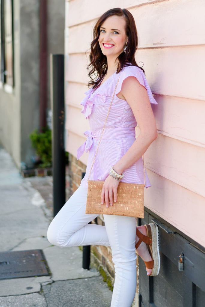 Life With Ashley T wearing pink ruffle top leaning against a downtown Charleston historic house