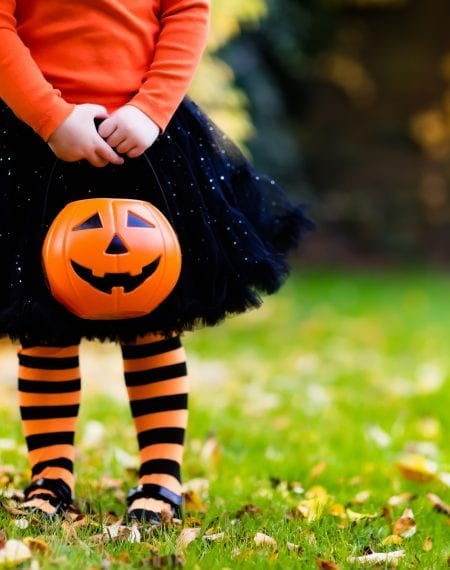 Little girl dressed in Halloween tights and a tutu holding a trick or treat pumpkin bag