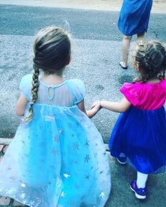Two young girls dressed as Elsa and Anna for Halloween