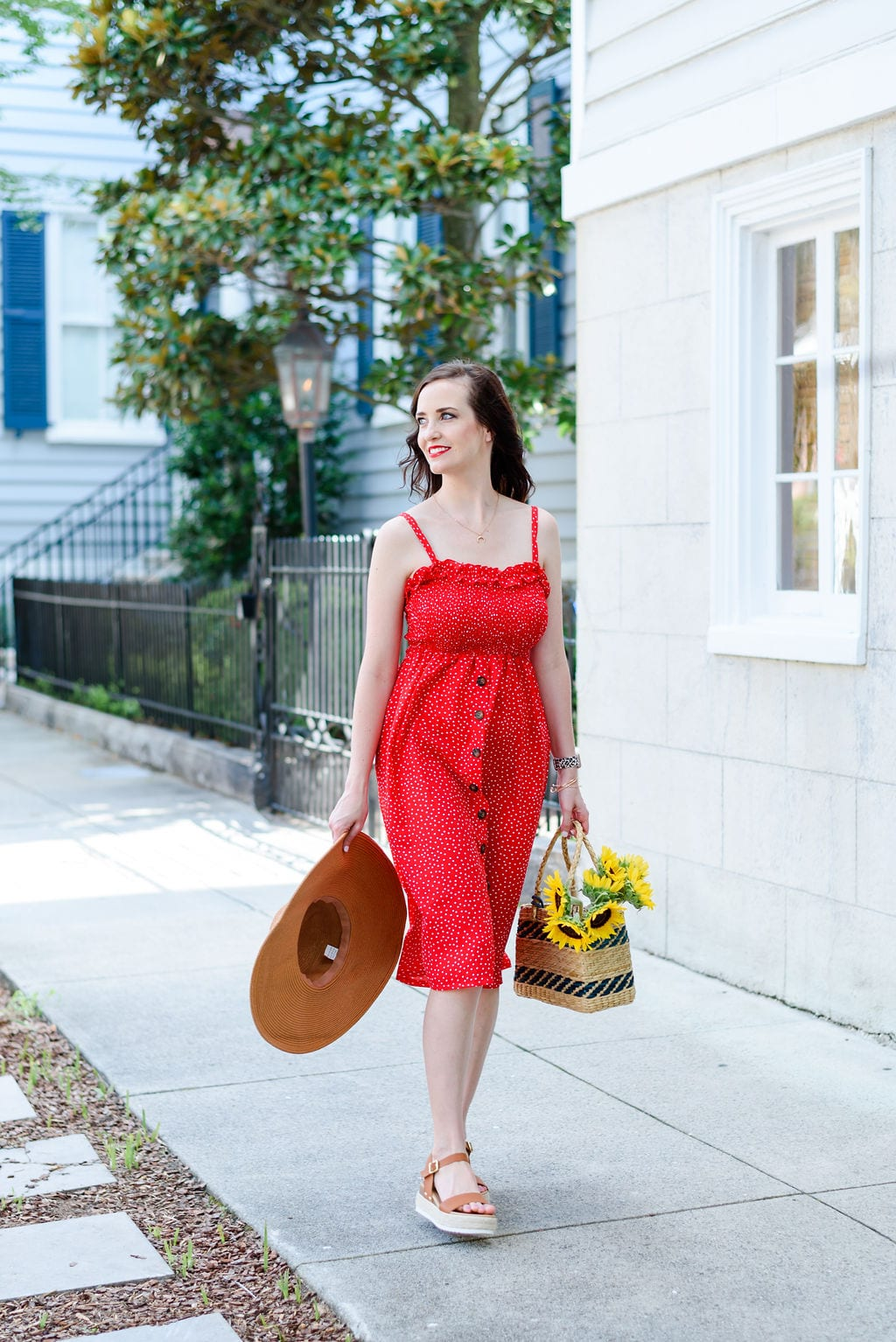 Ashley T walking downtown Charleston with a sun hat and sunflowers