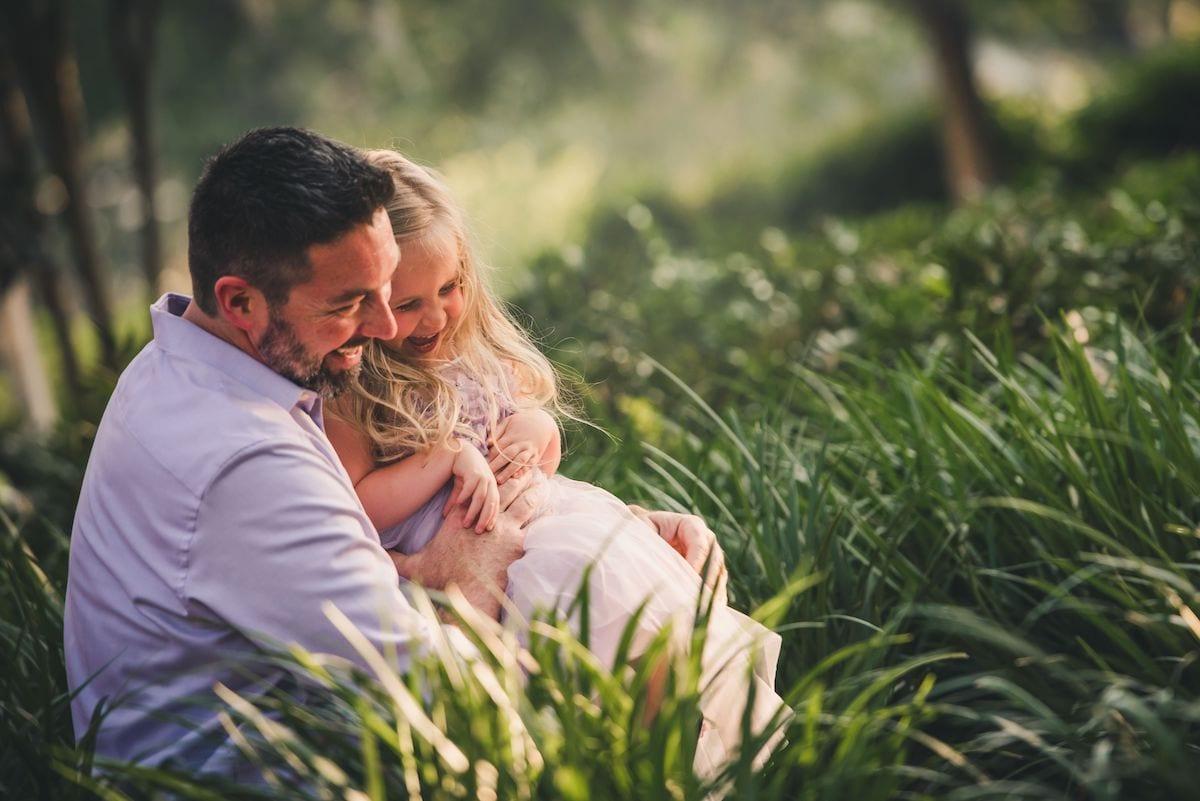 Daddy and daughter laughing in fielnd