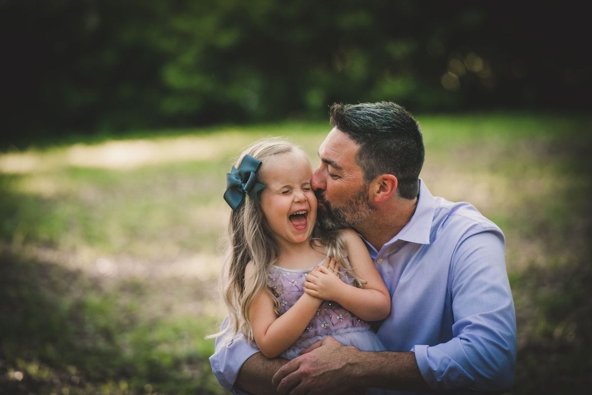 Daddy kissing daughter's cheek