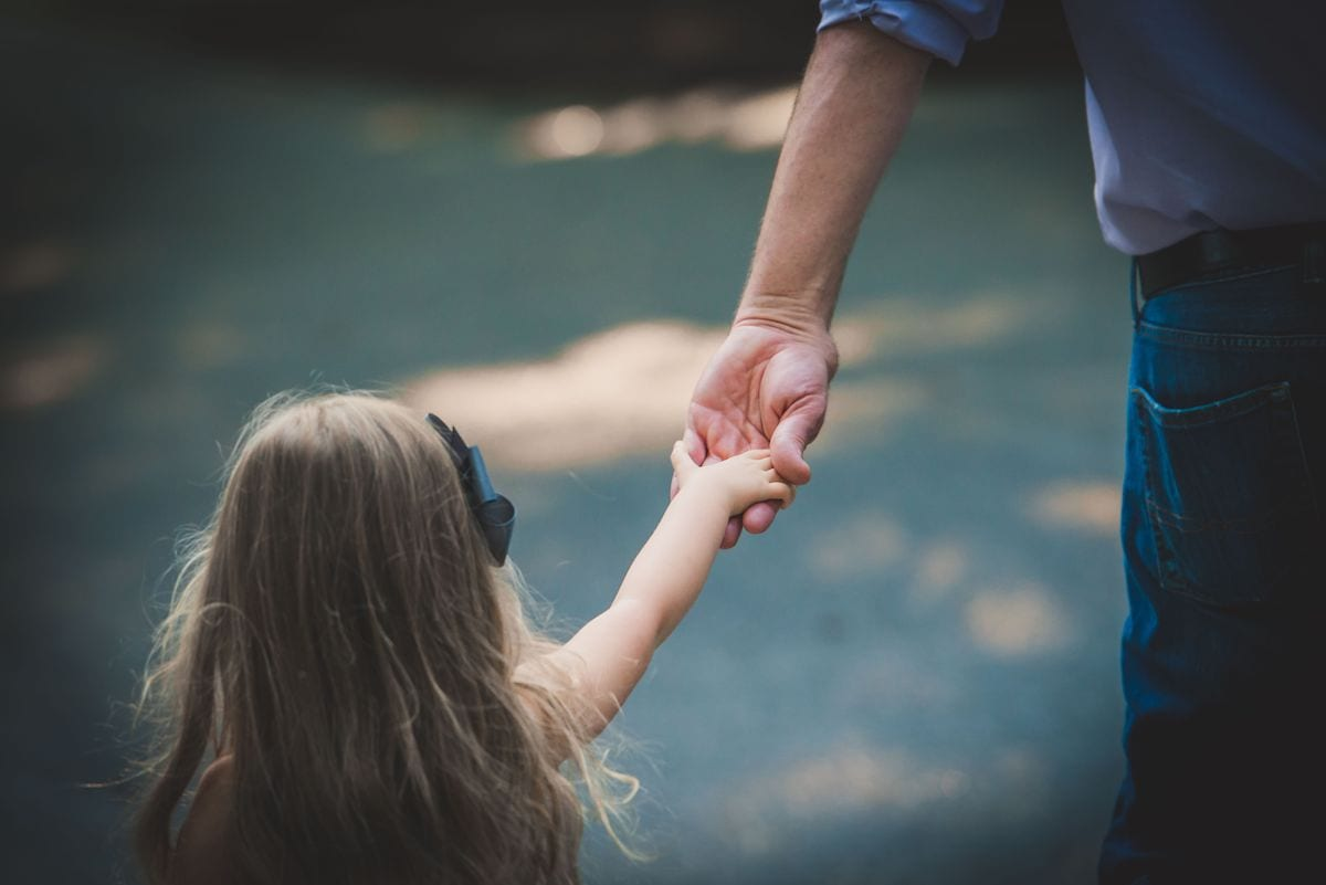 Daughter holding dad's hand