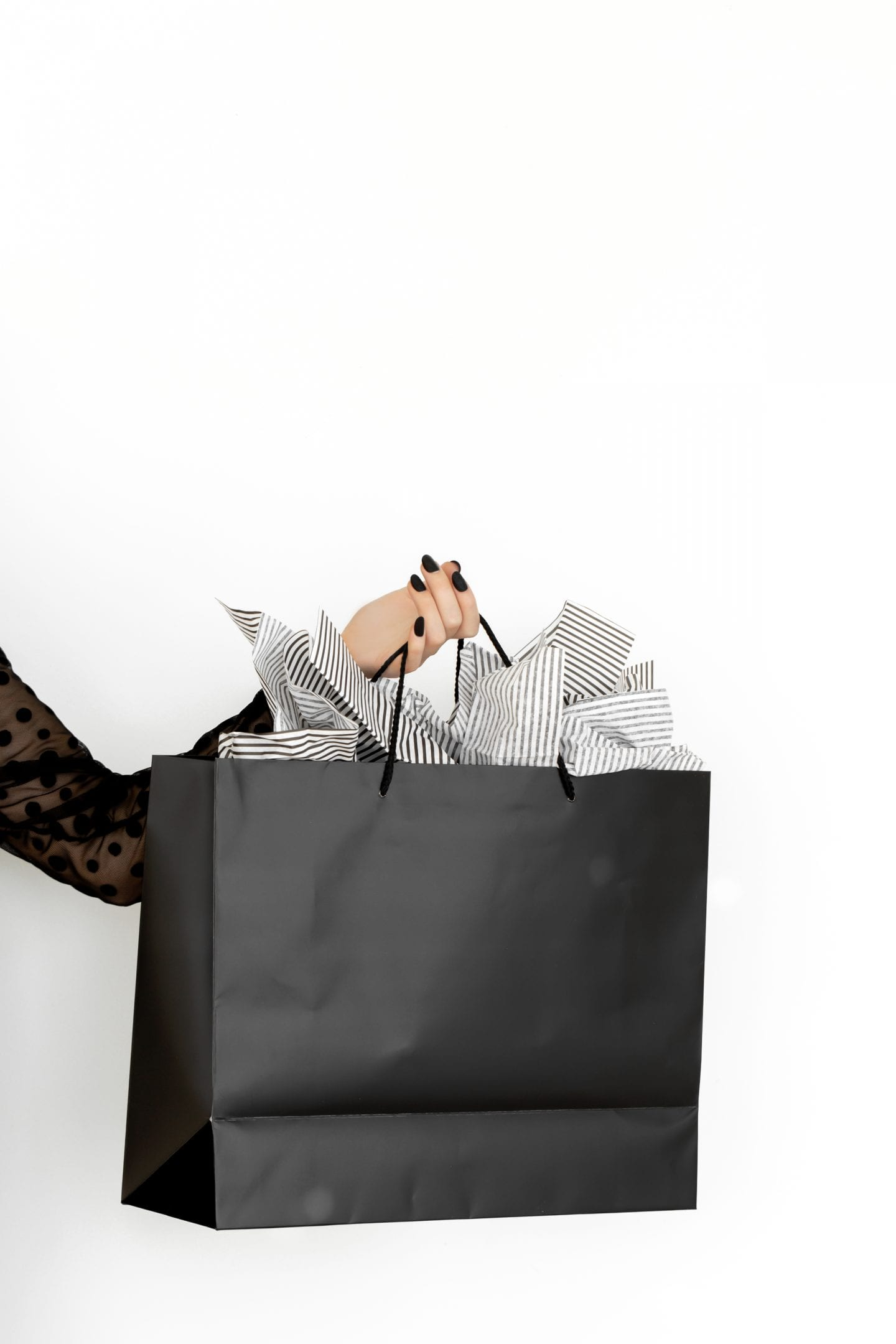 White woman holding a Black shopping bag with painted black nails